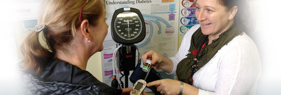 Female patient receiving instructions on blood sugar checking