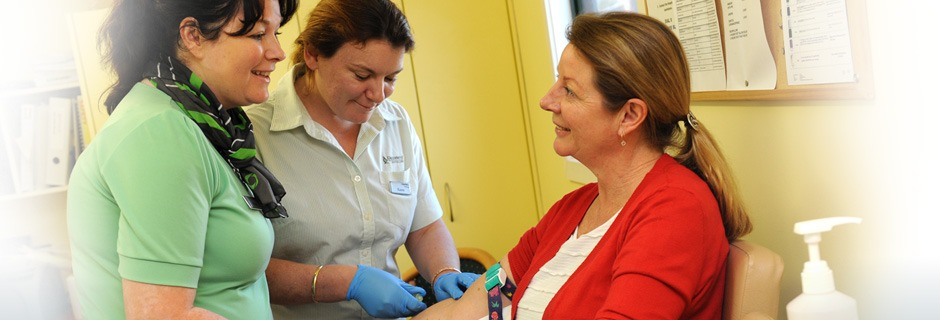Woman having blood drawn by nurse and chatting with team members